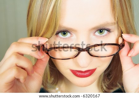 Young blond businesswoman looking over her black rim glasses - stock photo