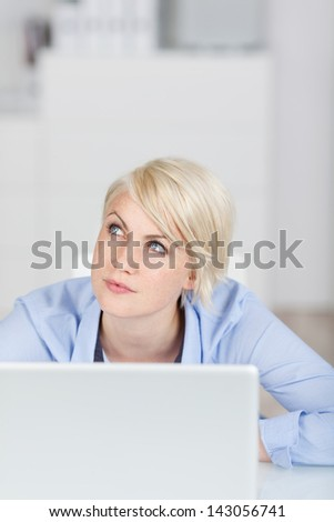 Young blond businesswoman looking up thoughtfully in front of a notebook computer at office desk - stock photo