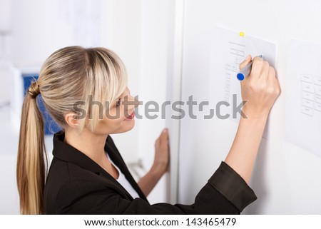 Young blond businesswoman writes something on the chart - stock photo