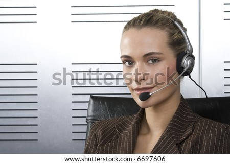 Young blond call center agent talking on the headset in a modern office setting - stock photo