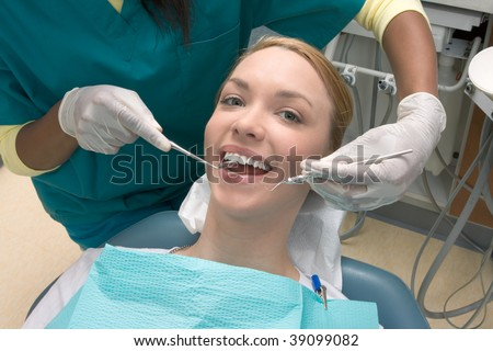Young blond Caucasian female opening her mouth while African-American ethnic dentist in white latex gloves check condition of her teeth - stock photo