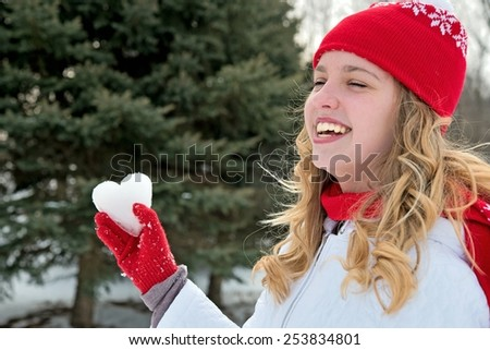 young blond Caucasian girl with ice heart wearing a red glove - stock photo