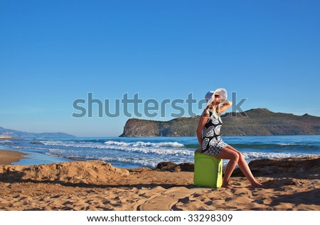 Young blond caucasian woman wearing white straw hat and sunglasses sitting on green suitcase on a beach. - stock photo