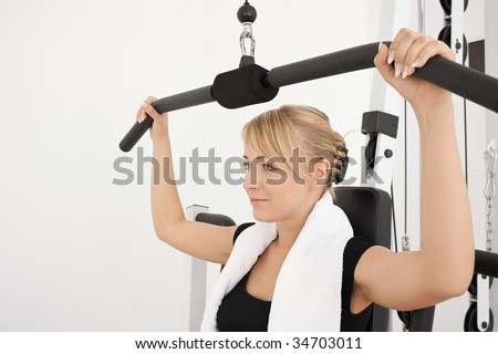 Young blond caucasian woman working out in gym. Pumping iron while sitting. Serious facial expression.