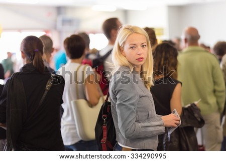 Young blond caucsian woman waiting in line with plain ticket in her hands. Lady standing in a long queue to board a plane. - stock photo