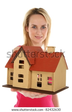 Young blond estate agent lady holding out a model house - concept
