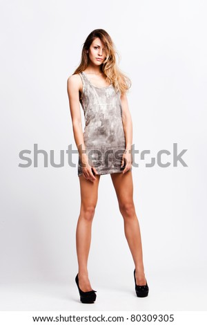 young blond fashion model in short dress on high heels, studio shot - stock photo