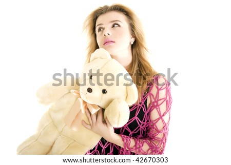 Young blond fashionable girl posing with teddy bear in studio isolated