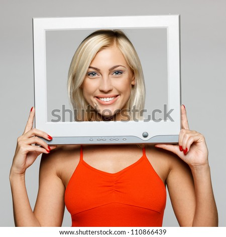 Young blond female looking through the TV / computer screen frame, smiling, over gray background