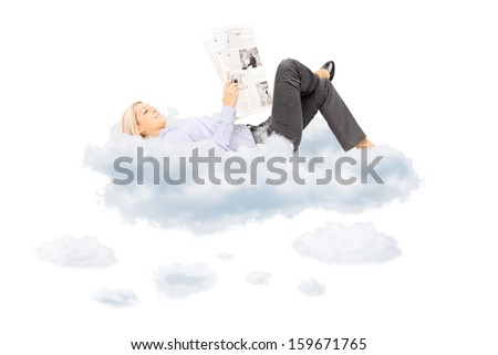 Young blond female reading a newspaper and lying on clouds, isolated on white background - stock photo