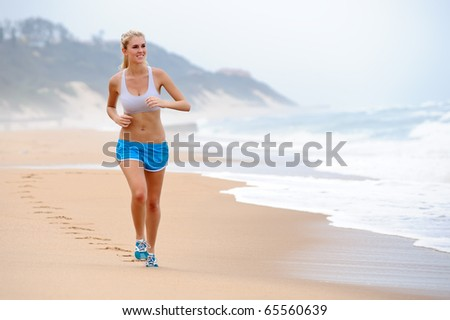 Young blond female runs along the beach - stock photo