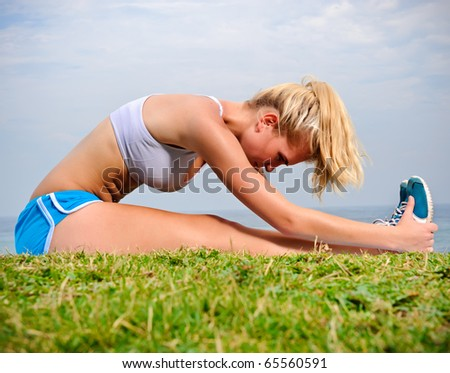 Young blond female stretches her leg on the grass - stock photo