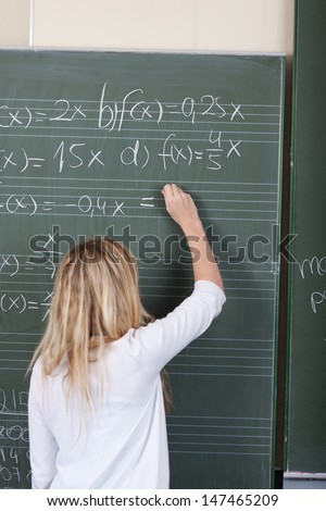 Young blond female student solving maths equations standing with her back to the camera writing on the blackboard at school