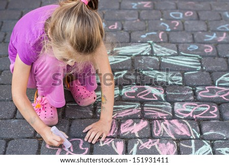 Young blond five years old caucasian girl drawing a picture outdoor on the pavement with chalk - stock photo