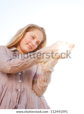 Young blond girl holding the sun in her hands, with sun rays filtering through, against a blue sky. - stock photo