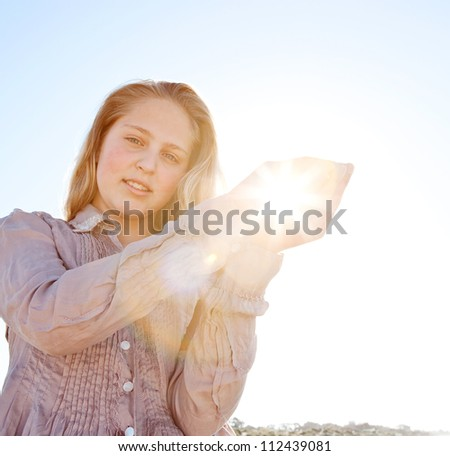 Young blond girl holding the sun in her hands, with sunrays filtering through, against a blue sky. - stock photo