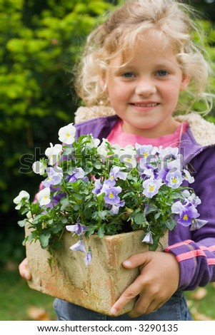 Young blond girl holds a pot of violet flowers in her hands.