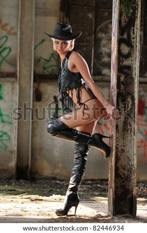 young blond girl in black cowboy hat and hi-heel boots posing sexy in hangar