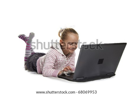 Young blond girl playing with laptop isolated over white - stock photo
