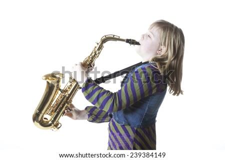 young blond girl plays alto saxophone against white background  in studio - stock photo