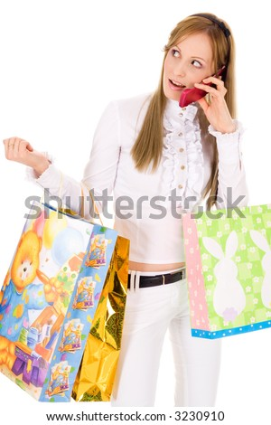 Young blond girl shopping and speaking on the phone isolated on white background