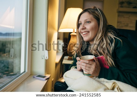 Young Blond Girl Sitting in Chair with book looking out the window and smiling