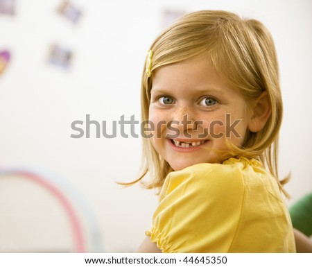 Young blond girl smiling over shoulder at viewer. Vertically framed shot. - stock photo