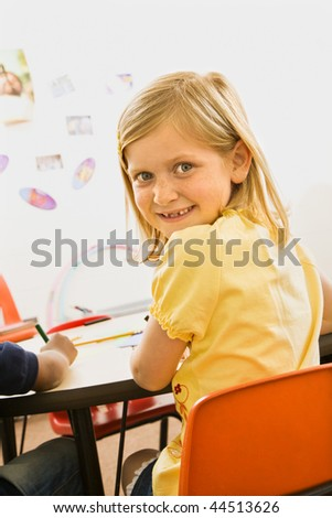 Young blond girl smiling over shoulder in elementary classroom. Vertically framed shot. - stock photo