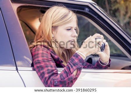young blond girl takes a photo from a car - stock photo