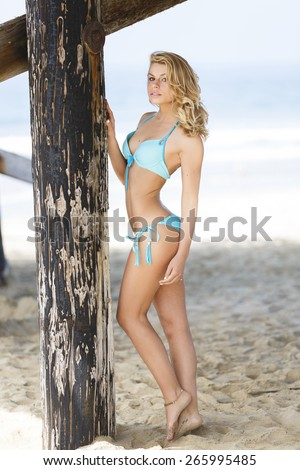 Young blond girl wearing bikini outfit posing at the beach - stock photo