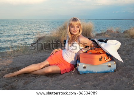 Young blond girl with her luggage sitting nicely in the sand on the beach. She came to the warm country to relax. Light of the sun at sunset. - stock photo