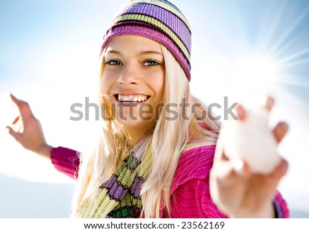 young blond girl with snowball - stock photo