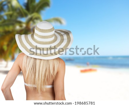 Young blond girl with straw hat looking on sandy beach - stock photo