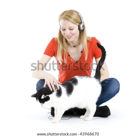 Young blond hair woman in headphones relaxing with her lovely cat - stock photo