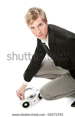 Young blond handsome man changing sound volume at boombox; isolated on white - stock photo