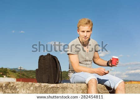 Young blond handsome man relaxing outdoors in summer sitting wearing denim shorts, gray shirt and canvas shoes with headphones and takeaway coffee. Square format, retouched, filter applied. - stock photo