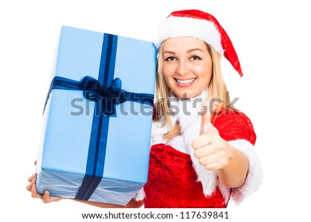 Young blond happy woman in Christmas Santa costume holding big blue gift box and gesturing thumb up, isolated on white background. - stock photo