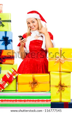 Young blond happy woman wearing Christmas Santa costume with mobile phone, surrounded by gift boxes, isolated on white background. - stock photo
