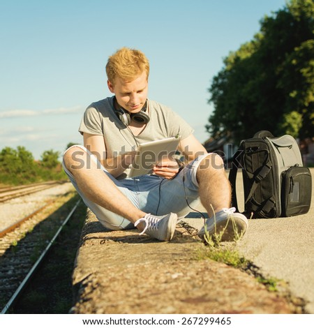 Young blond hipster man with digital tablet and headphones outdoors in summer sitting near railway on sunny summer day. Handsome teenage guy relaxing in park. Square format, mild retouch, no filter. - stock photo