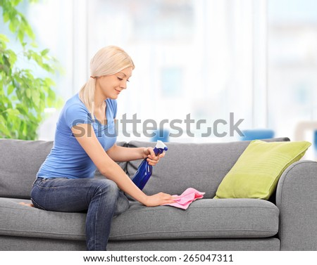 Young blond housewife cleaning a couch with a rag and a cleaning spray at home - stock photo