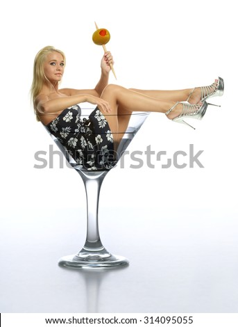 Young blond in a martini glass holding an olive isolated on a white background - stock photo