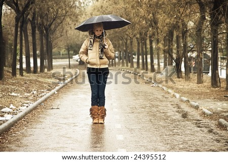 Young blond in walkway under rain - stock photo