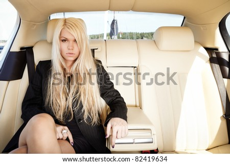 Young blond lady sitting on a backseat of a luxury car - stock photo