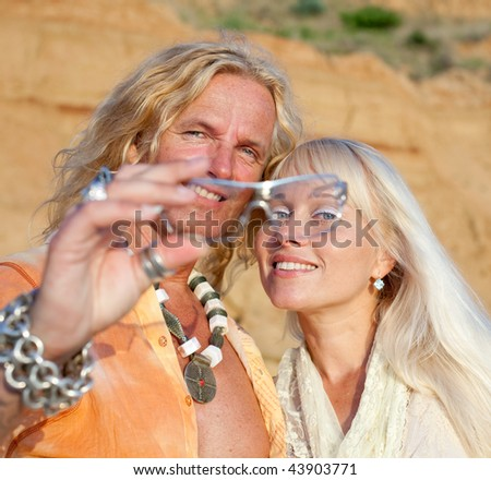 Young blond man and blond woman  are looking  at camera through a sunglasses - stock photo