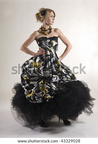 Young blond model in a colorful gown on white background - stock photo