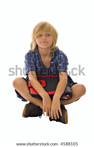 young blond preteen boy sitting cross-legged on white background holding red and black notebook