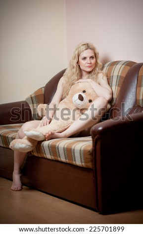 Young blond sensual woman sitting on sofa relaxing with a huge teddy bear. Beautiful girl with comfortable clothes relaxing on the couch with a toy. Attractive blonde in cosy scenery indoor - stock photo