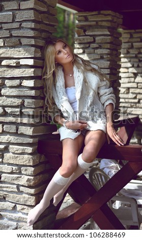 young blond sexual woman with long curly hair sitting  on the wooden railing - stock photo