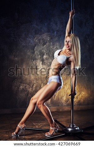 Young blond sexy pole dance woman on old wall background
