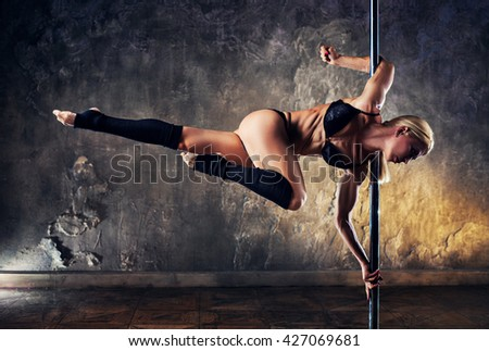 Young blond sexy pole dance woman on old wall background - stock photo